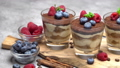 Tiramisu dessert with blueberries and raspberries in a glass on wooden cutting board 54510541