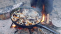Tourist fried mushrooms and onions in a pan over the fire. Campfire in the woods. 54558790