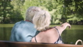 Back view of a happy mature couple sitting on the bench near the river, admiring nature, pointing 54566603