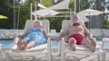 Elderly positive couple lying on sunbeds near the pool holding hands and smiling. Happy loving 54566612
