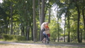 Happy mature couple walking in the park together. Elegant senior woman holding parasol. Old man and 54566623