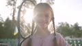 Portrait cute little smiling girl with pigtails and a tennis racket on her shoulder looking into the 54566630