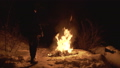 Man throws jacket into campfire on nature at night 54593224