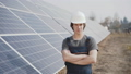 Portrait of serious engineer stands at solar batteries with crossed hands 54593386