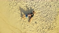 Aerial Top view of couple lying on white sand beach and azure sea taking a sunbath in summer 54829345