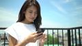 青い空の下で携帯電話を操作する若い日本人女性 コピースペースあり 54868955