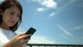 青空の下スマートフォンを操作する女性のアップ(右コピースペース) 54868958