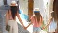 Happy mother and little adorable girls on cozy street during italian vacation. 54889596