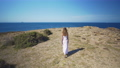 Aerial view. A girl in a white dress goes to the edge of the sea. 54894954