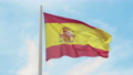 Flag of Spain. Red and yellow Spanish flag waving in the wind on a flagpole against the clear blue 54894956