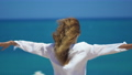 Back view of young woman with wind in her hair raising her hands on top of cliff above beautiful sea 54898807