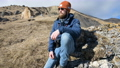 Portrait of a bearded traveler photographer in sunglasses and a cap sits on a rock with mirror 54905516