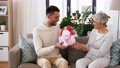 son giving present and flowers to senior mother 54913681