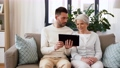 old mother and adult son with tablet pc at home 54913684
