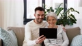 old mother and adult son with tablet pc at home 54913685