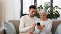 old mother and adult son with smartphone at home 54913686