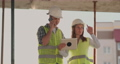 Building in construction with a female and a male builders, constructors, engineers walking along it 54935394