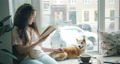 Attractive girl dog owner reading book and stroking pet on window sill in cafe 54946173