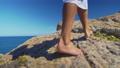 Bare female legs walking feets on rocky terrain. 54975321
