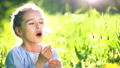 Beautiful little girl blowing dandelion at summer day. 55019516