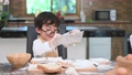 Cute little Asian boy sifting dough flour with sif 55037186