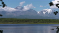 Volcanoes, clouds drifting sky, reflection in lake 55065090