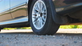 Detail view on wheel of powerful car starting movement and slipping on asphalt road. Small stones 55117022