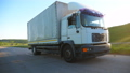 Truck with cargo trailer riding on highway and transporting goods at sunset time. Lorry riding 55123157