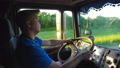 Profile of lorry driver riding through countryside in evening. Man in hat controlling his truck and 55182722