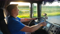 Profile of lorry driver riding through countryside at sunset time. Man in hat controlling his truck 55182725