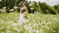 Smiling young girl in wreath with flowers bouquet standing on flowering field. Beautiful girl posing 55205320