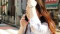 スマホで通話しながら歩く女性 通勤 ビジネスウーマン 55211930