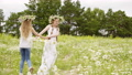 Two teen girls with flower wreaths play in meadow hold hand and spinning around. 55370999