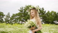 Teen girl with close eyes and with wreath on head and bouquet at flower meadow. 55380182