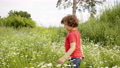 Curly boy walking on flowering field at summer day. Cute little boy walking on grass meadow at 55439154