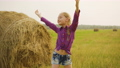 Happy girl stretching hand to sky on hay stack background. Teenager girl raising hands enjoying 55439166