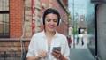 Portrait of lady enjoying music in headphone using smartphone outdoors walking 55459257