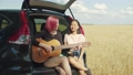 Hipster women playing guitar sitting in car trunk 55465259
