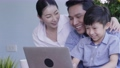 Asian family laughing and looking digital laptop 55593457