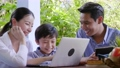 Asian family laughing and looking in tablet 55593458