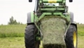 Green tractor picks up stack of grass with metal arms at farm field 55878291