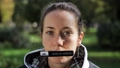 Portrait of young woman with nameplate sticked to her mouth looking at camera. 55911562