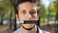 Face of young attractive man looking at camera with sticked nameplate on mouth 55911576