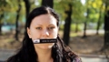 Young brunette woman with long hair and nameplate on her mouth looks at camera. 55911580