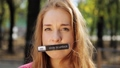 Cute young woman with long hair and nameplate on her mouth looks at camera. 55911581