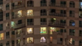 Windows of the multi-storey building with lighting inside and moving people in apartments timelapse. 55930491