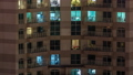 Windows of the multi-storey building with lighting inside and moving people in apartments timelapse. 55930493