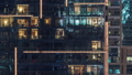 Lights in windows of modern multiple story building in urban setting at night timelapse 55931110