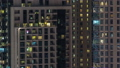 Windows of the multi-storey building with lighting inside and moving people in apartments timelapse. 55931112