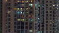 Windows of the multi-storey building with lighting inside and moving people in apartments timelapse. 55931114